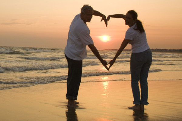 a happy couple making a heart shape with their arms on a beach