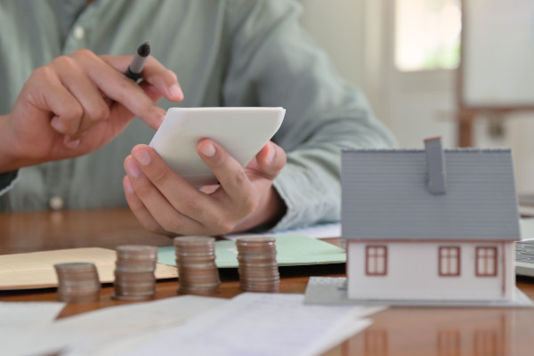a person calculatingtheir mortgage on a handheld calculator