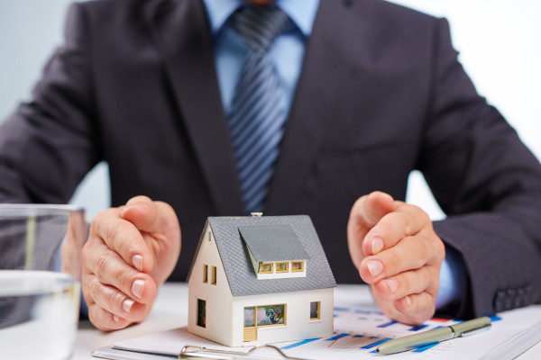a man wearinga suit with is hands around a model house