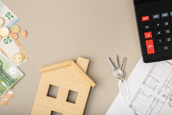 a wooden house, calculater, euros and house plans on top of a table